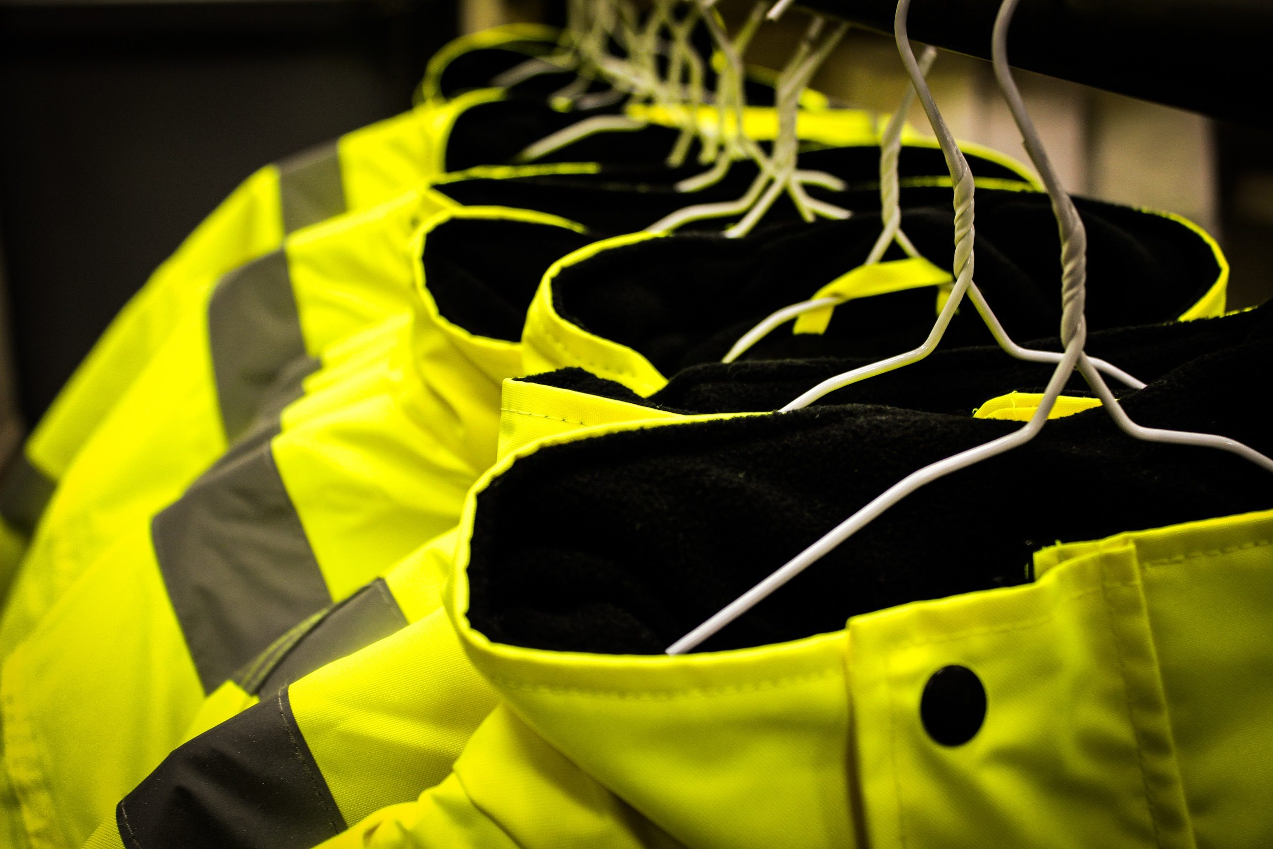 Yellow safety fluorescent jackets hanged up. Multiple jackets.